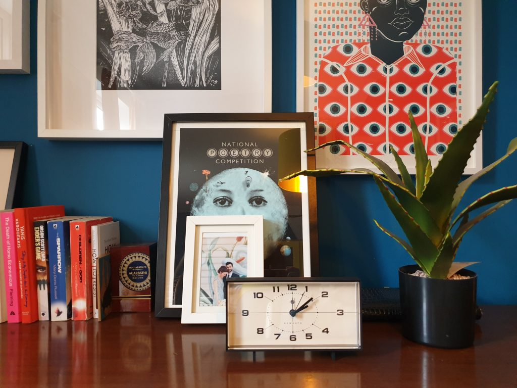 Newgate 60s style clock on blue wall with plant and books