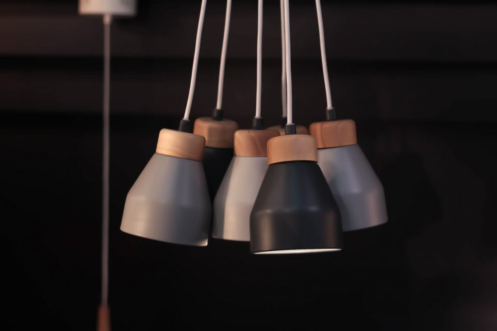 image shows a cluster og grey pendant lights in a dimly-lit space