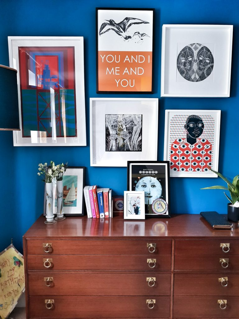 blue gallery wall with orange graphic prints