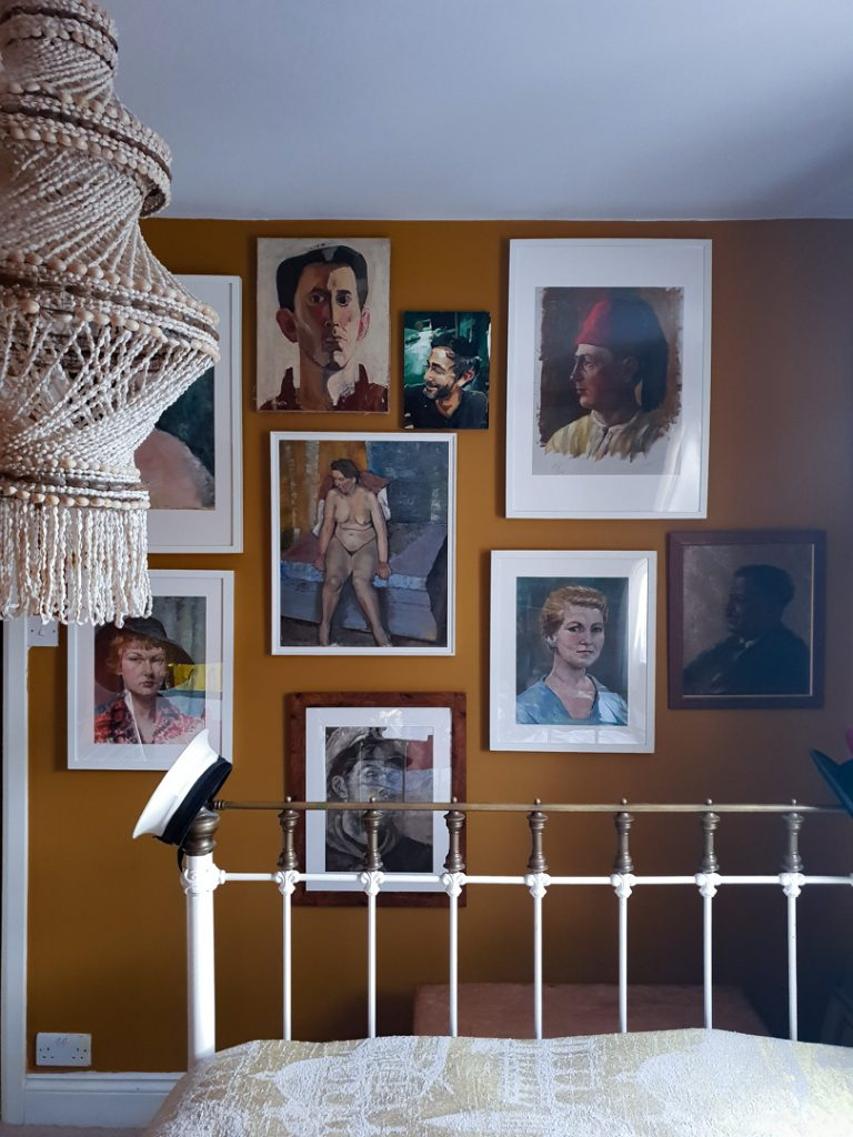 Gallery wall of oil portraits on a mustard wall