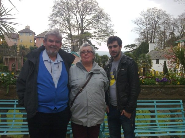 An old lady, and old man and a young man in a welsh country village standing in front of a bench