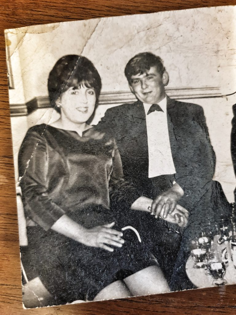 a photo of a woman with a beehive and a man in a suit smiling