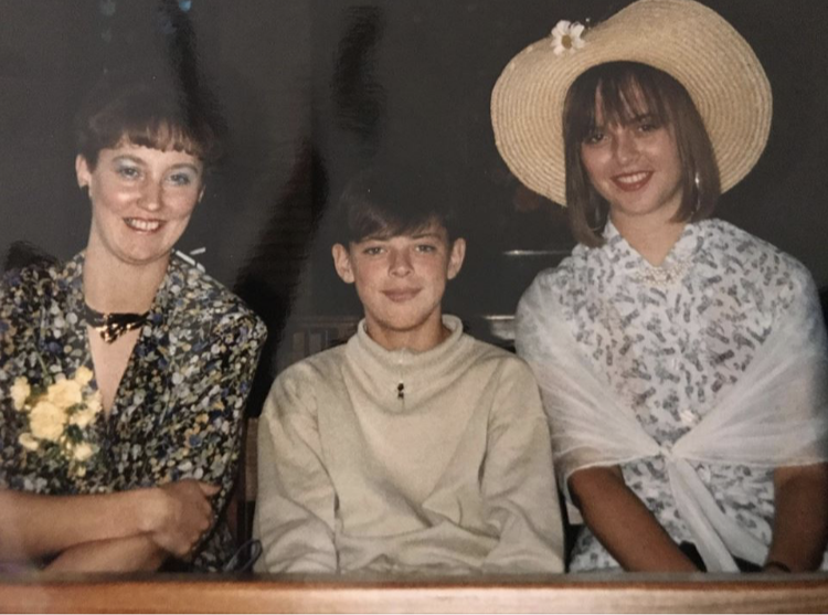 Woman in a floral shirt, boy in a beige rollneck jumper and a girl in a large straw hat
