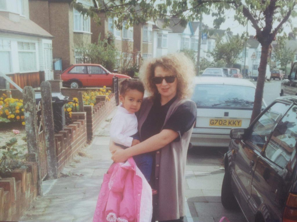a woman with curly hair and a pink jacket in her hand holds a toddler on a leafy street
