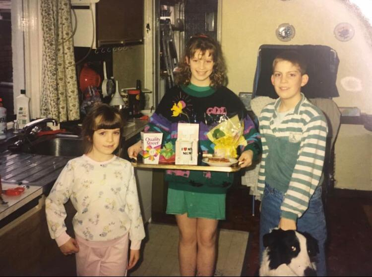 Three children in 80s clothes hold a tray of presents. There is a dog.