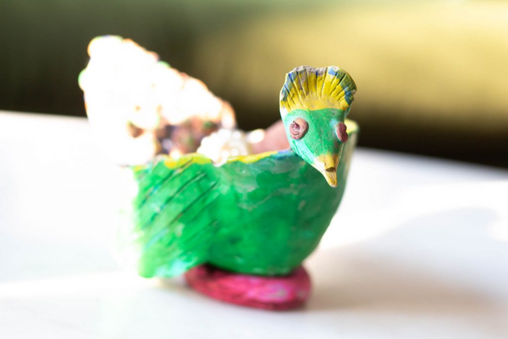 A green and yellow ceramic bird