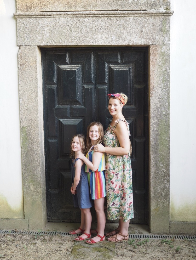 A woman standing in front of a door with her two daughters all in brightly patterned clothes
