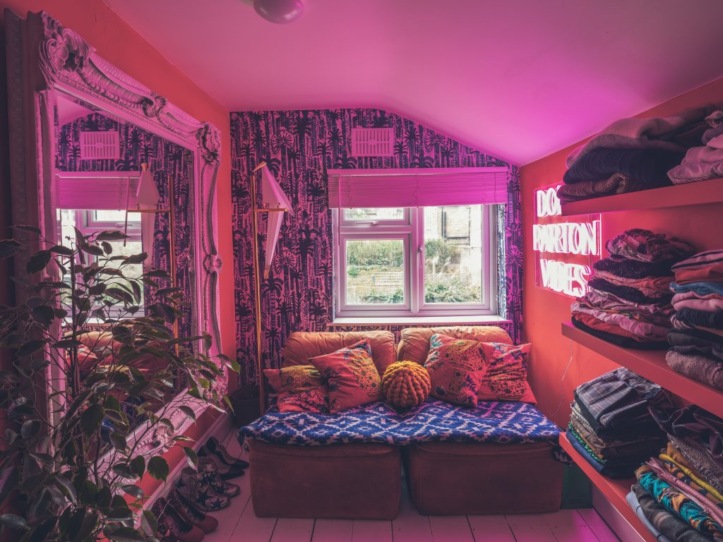 A room with red walls, blue and white botanical wallpaper, yellow rug, white baroque mirror, plant and bird lamp and lots of clothes and shoes  with the pink light of a Dolly Parton Neon