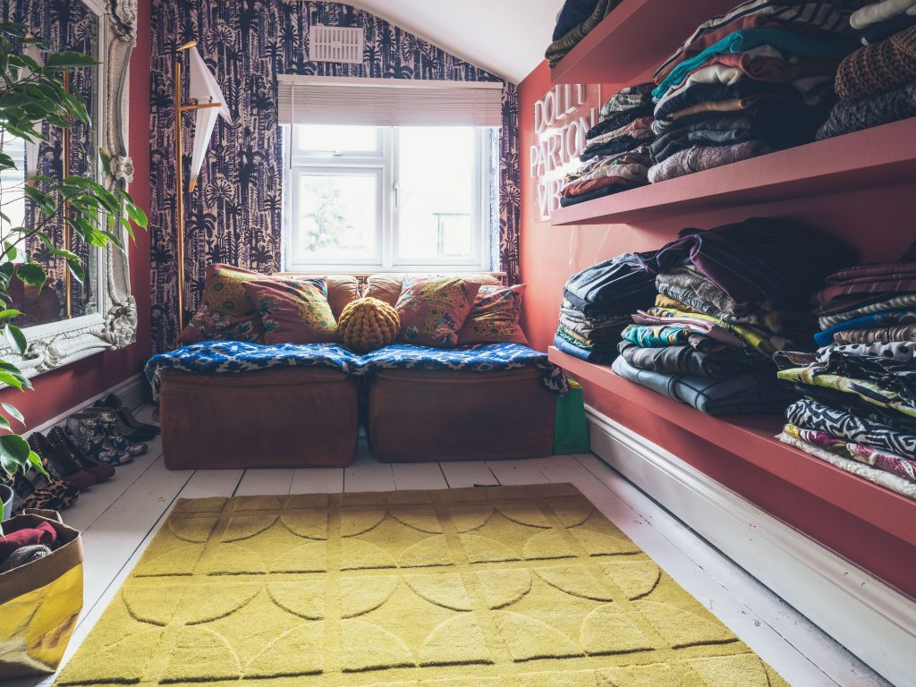 A room with red walls, blue and white botanical wallpaper, yellow rug, white baroque mirror, plant and bird lamp and lots of clothes and shoes