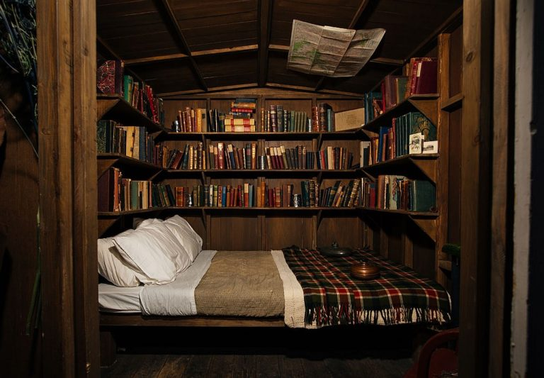 bed with tartan blankets surrounded by books