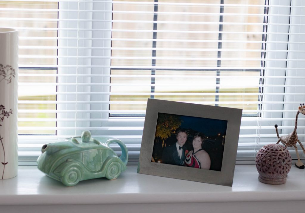 a photo and a ceramic car on a window ledge