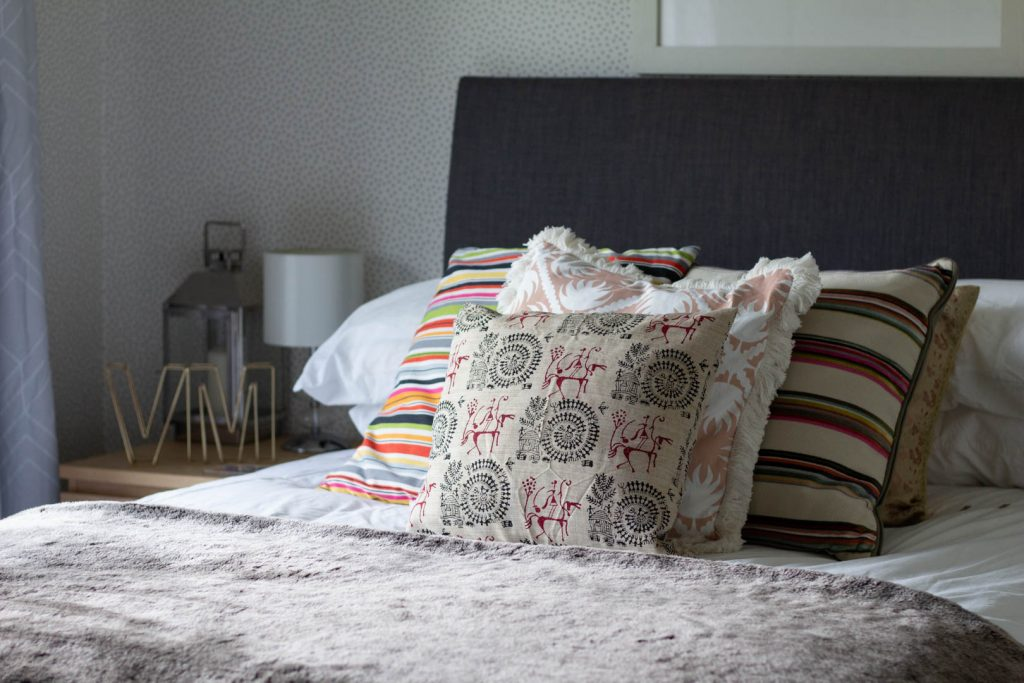 a bed with a grey headboard and lots of patterned cushions