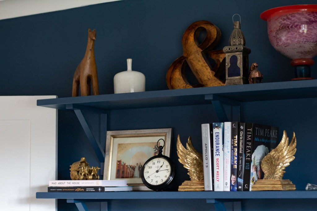 a shelf on a navy wall with lots of ornaments