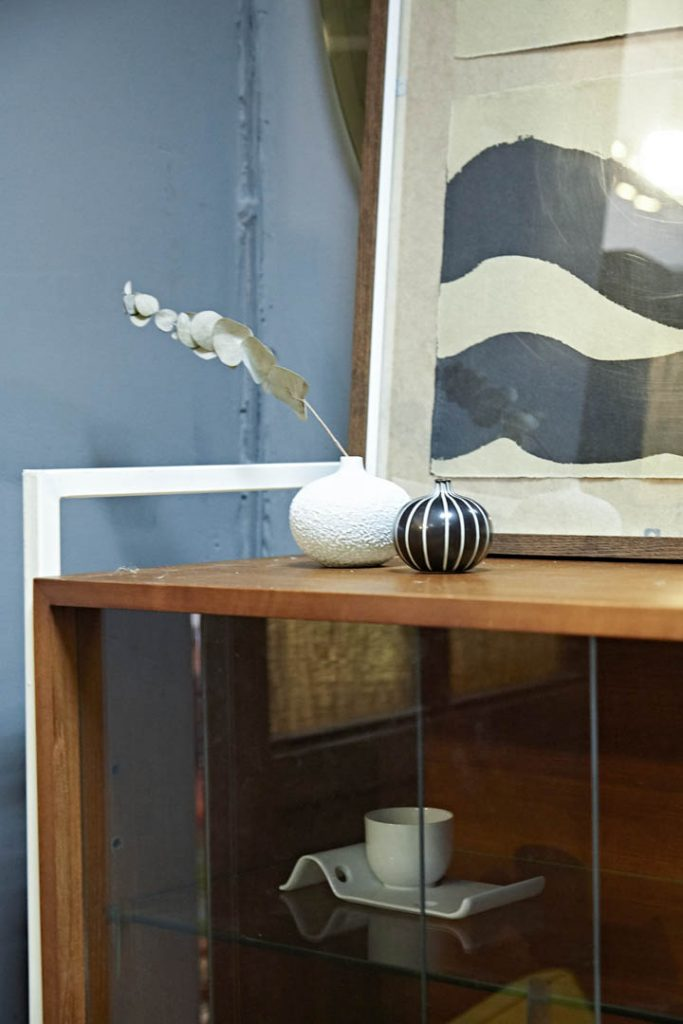 A small black and white vase on top of a teak bookshelf