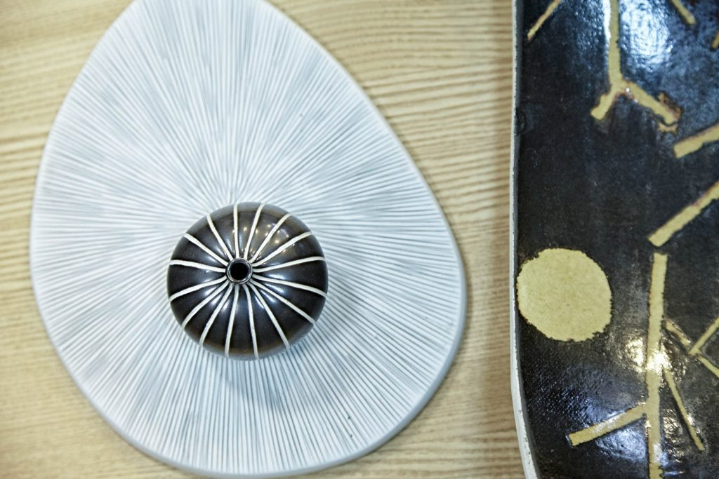 A black vase on a white plate on a wooden table
