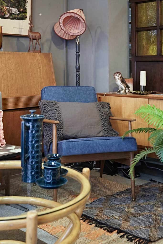 A blue chair with a bamboo and glass coffee table with coffee pot and blue and peach rugs with teak sideboards
