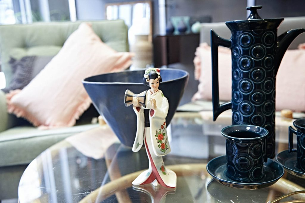 a blue teapot, geisha and blue bowl sit on a glass and bamboo coffee table