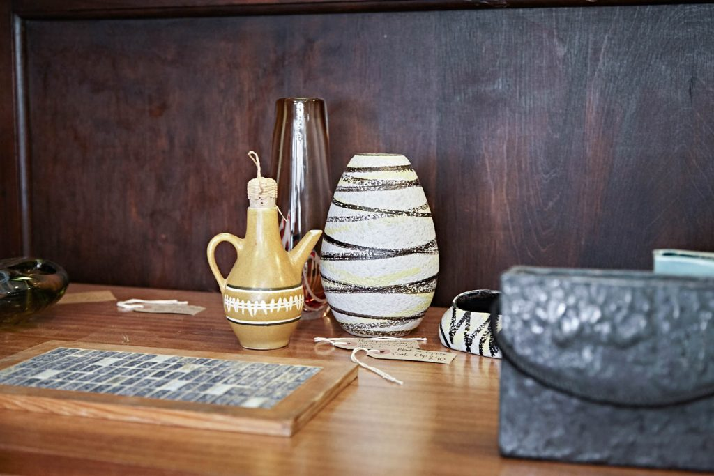 brown and cream patterned 60s vases sit on a wooden sideboard