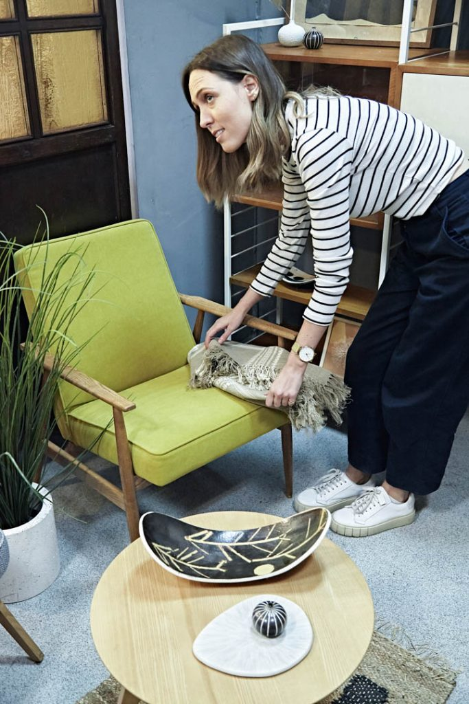 A woman in a striped top rearranges a green chair