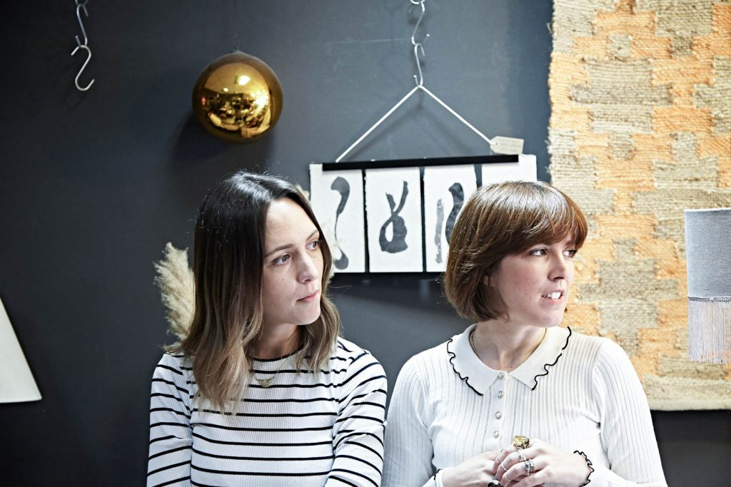 Two women stand against a grey wall with art hanging on it