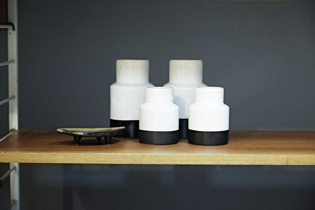 Monochrome vases on a wooden shelf