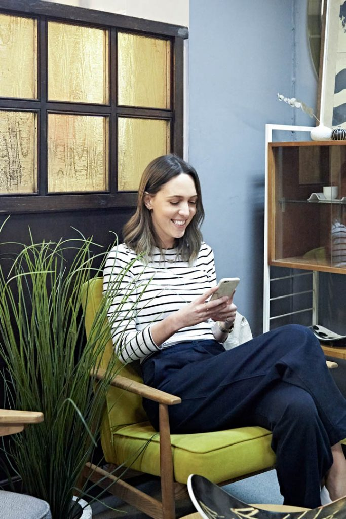 A woman in a striped top sits on a green chair looking at her phone