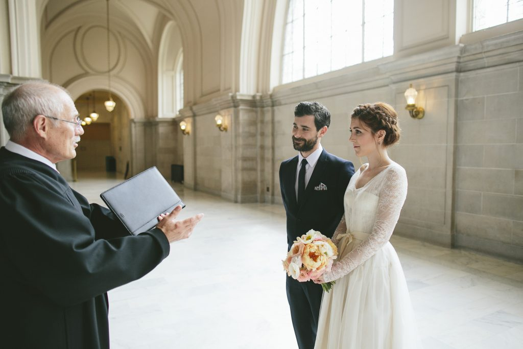 Bride, groom and officiant marrying them in city hall