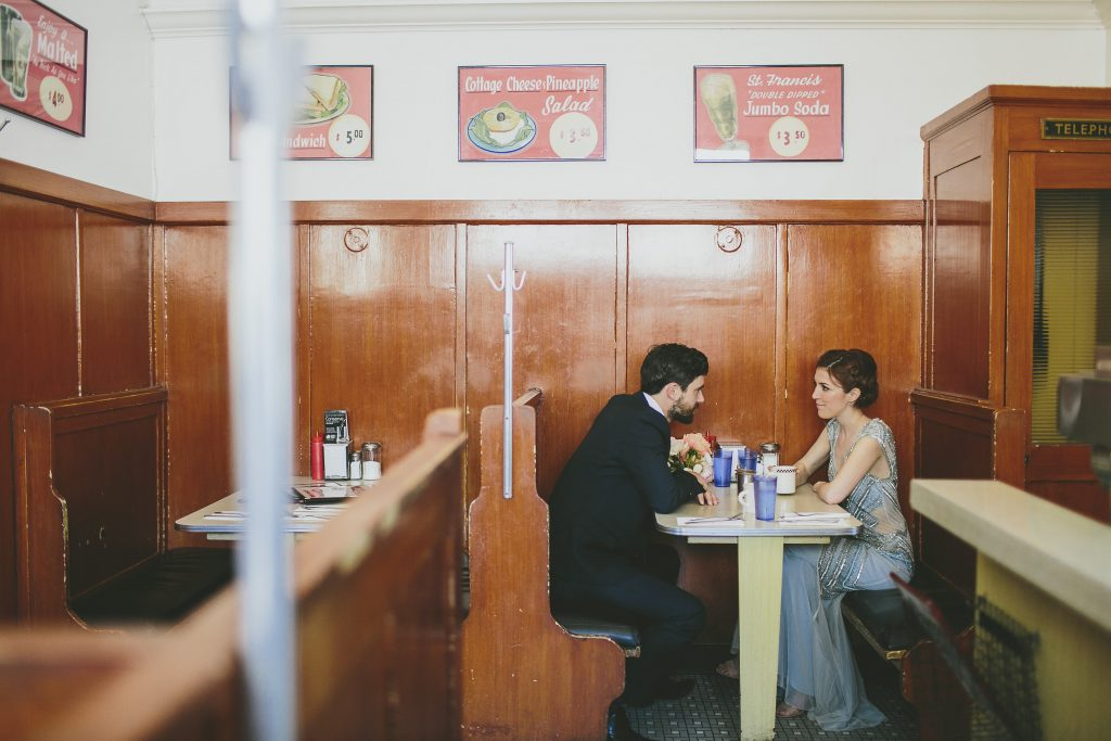 Couple sit in diner in evening wear
