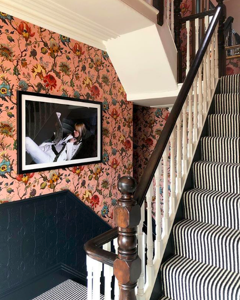 floral pink wallpaper on a victorian staircase with a striped runner
