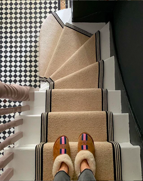 slippers on a stairway e with a beige runner and monochrome tiles at the bottom
