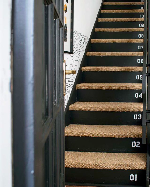 black staircase with number and patterned wallpaper