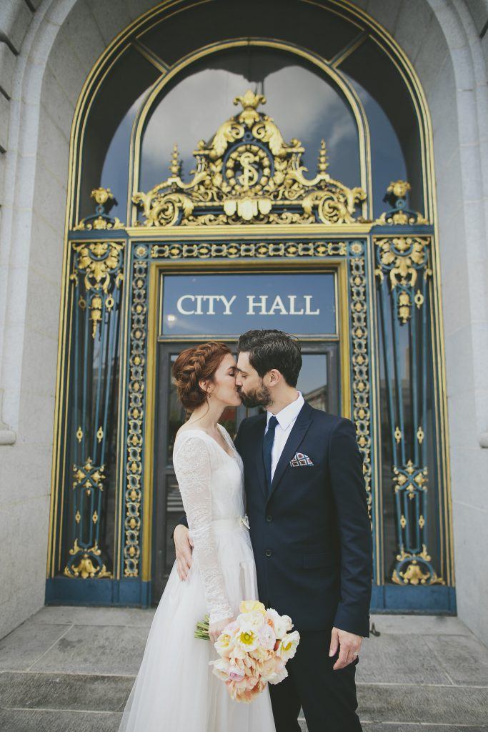 Bride and groom kissing outside San Francisco City Hall