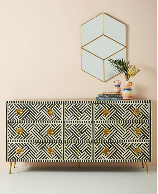 A black and white patterned sideboard on a pink wall with a cubist mirror on the walls