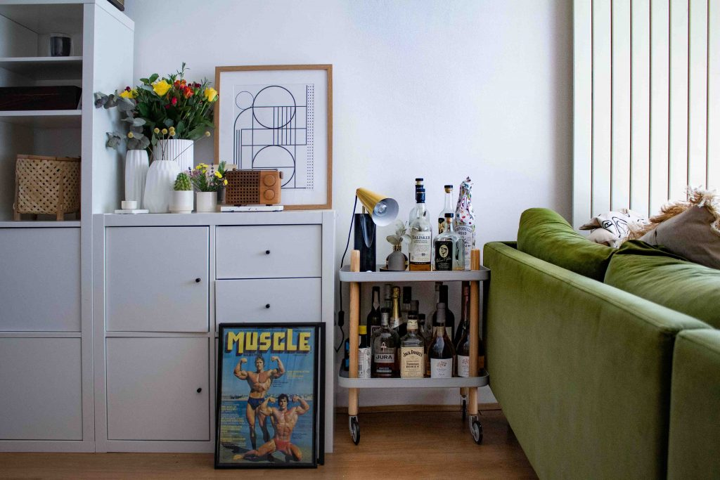 a green couch with a drinks cart next to it full of bottles. A white cupboard unit has flowers on it and a graphic monochrome print. A colourful muscle poster is on the floor