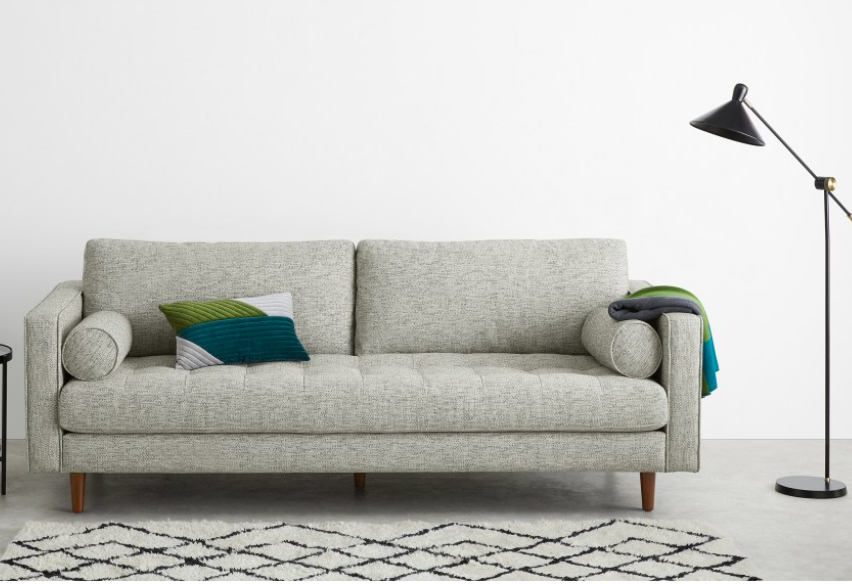 a grey sofa with green pillows on a white patterned berber rug with a black standing lamp