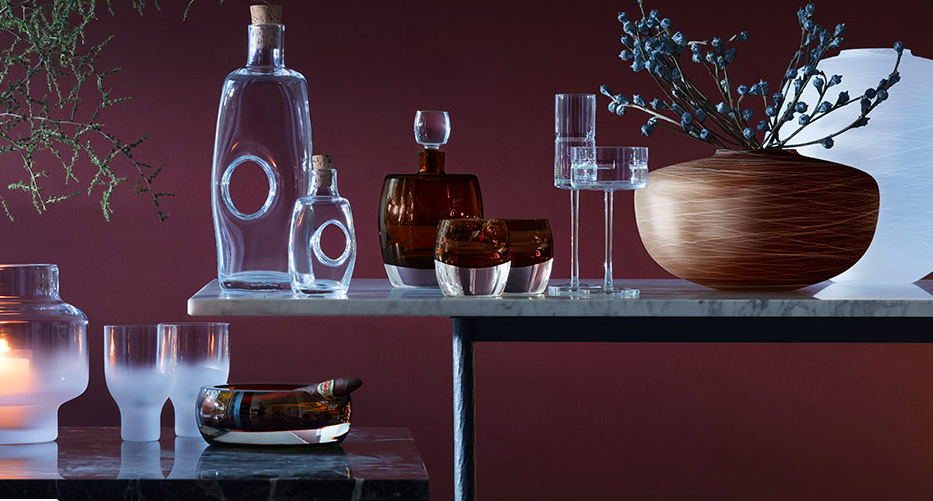 A pair of marble tables with decanters and glasses on it as well as vases with plants on a Burgundy wall.