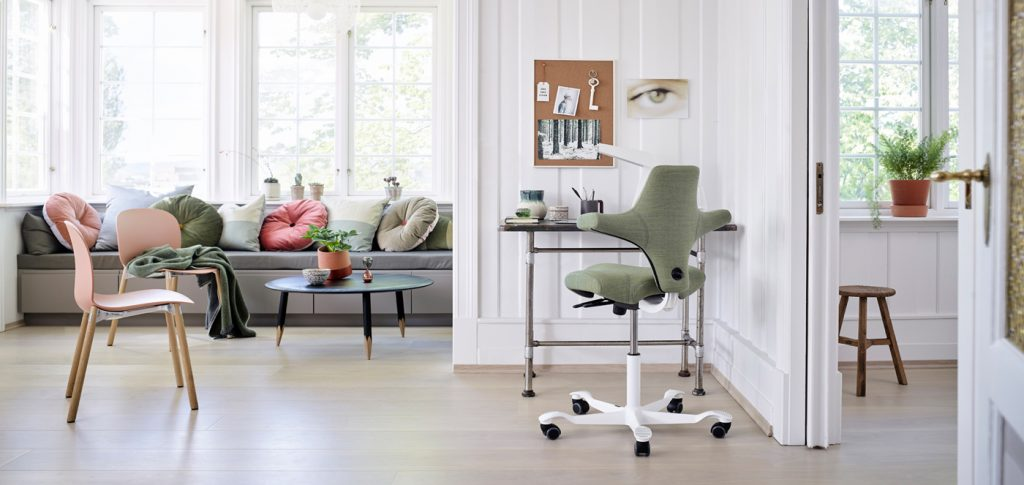a home office area with a desk made of scaffolding poles. A modern desk chair with green upholstery. A lounge area is next to it with chairs, a mid century coffee table and a sofa with lots of multicoloured cushions.