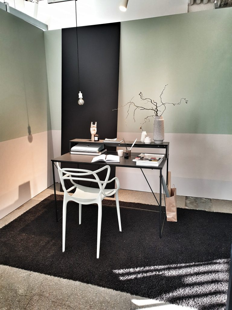 a black desk and white chair on a black rug with a wall that is white on the bottom and mint on the top behind it. There are books and bases with twigs on the desk