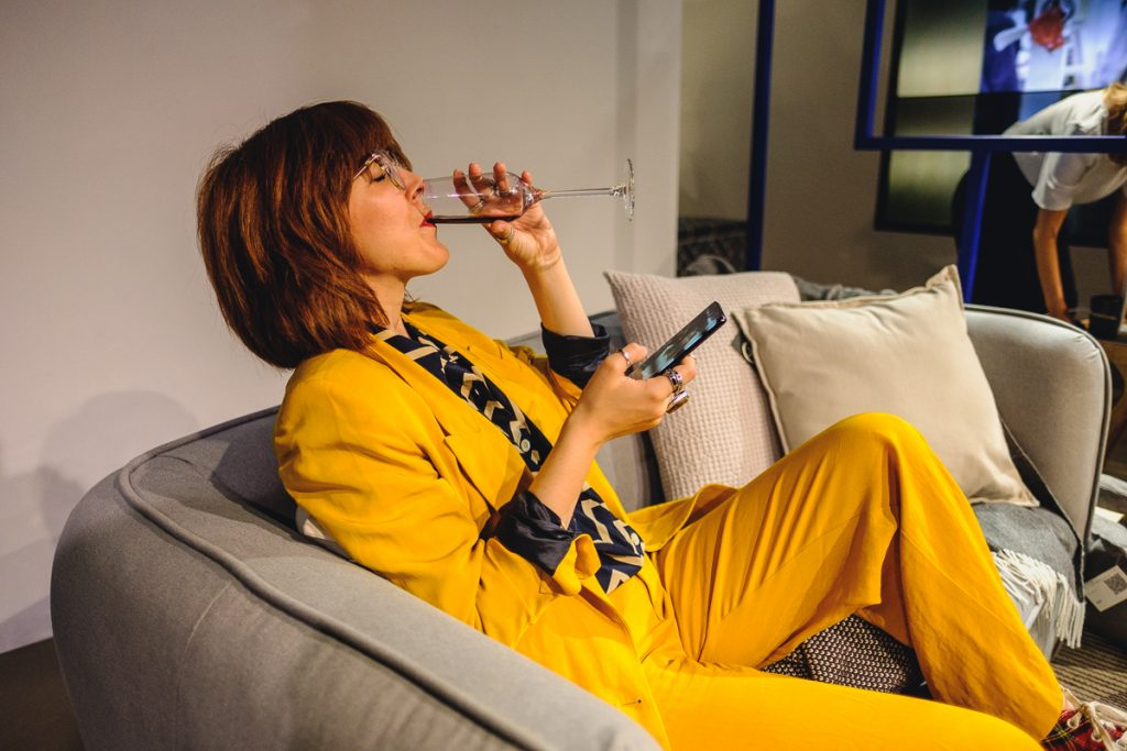 a woman in a yellow suit drinks from a champagne glass on a grey sofa