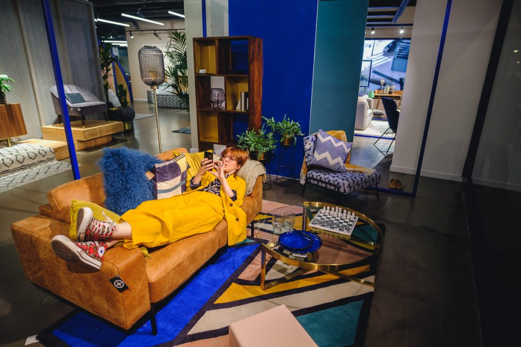 Image shows a woman in a yellow suit lying down on a brown sofa that sits on top of a brightly-coloured rug