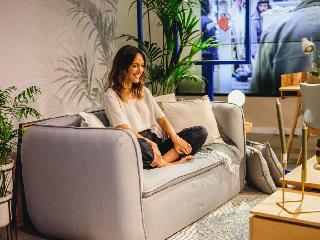Image shows a woman in a white T-shirt smiling inanely at nothing on a grey sofa in the Made.com showroom