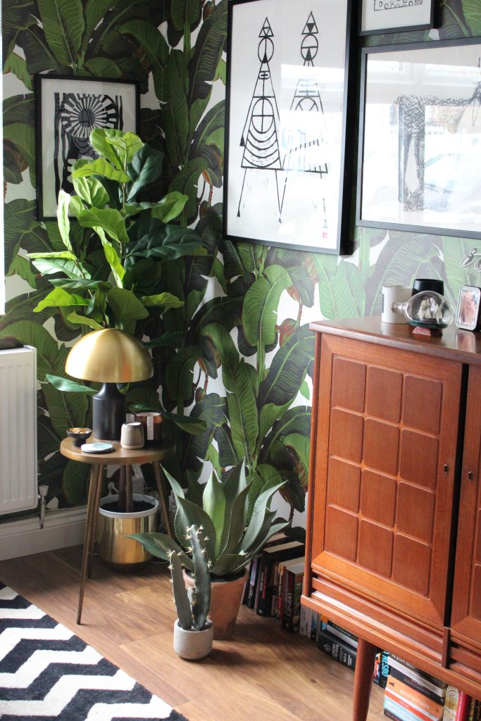 a brass lamp and coasters and candles on a bronze table against botanical wallpaper with a large plant behind.  A teak cabinet is next to it with lots of books on the flooe
