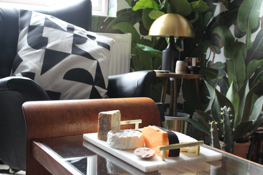 a brass lamp and coasters and candles on a bronze table against botanical wallpaper. a black leather chair with a monochrome cushion and a marble cheeseboard with cheese on a glass and teak coffee table