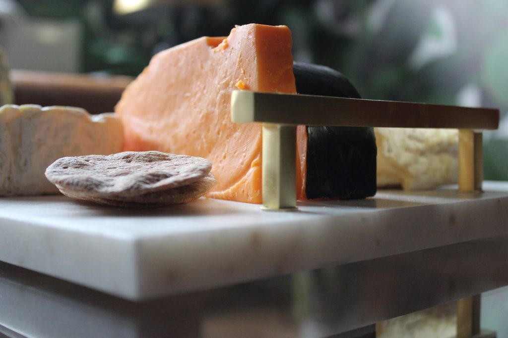 a variety of cheese and biscuits on a marble cheeseboard with brass handles