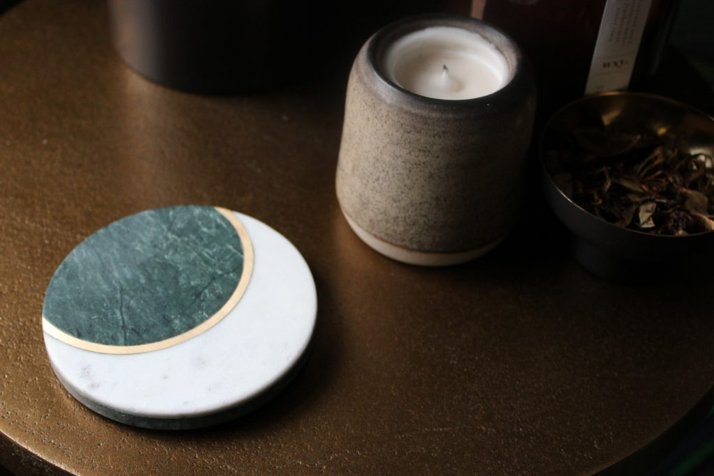 A marble moon coaster sits on a burnished copper table with a candle and a bowl of potpourri