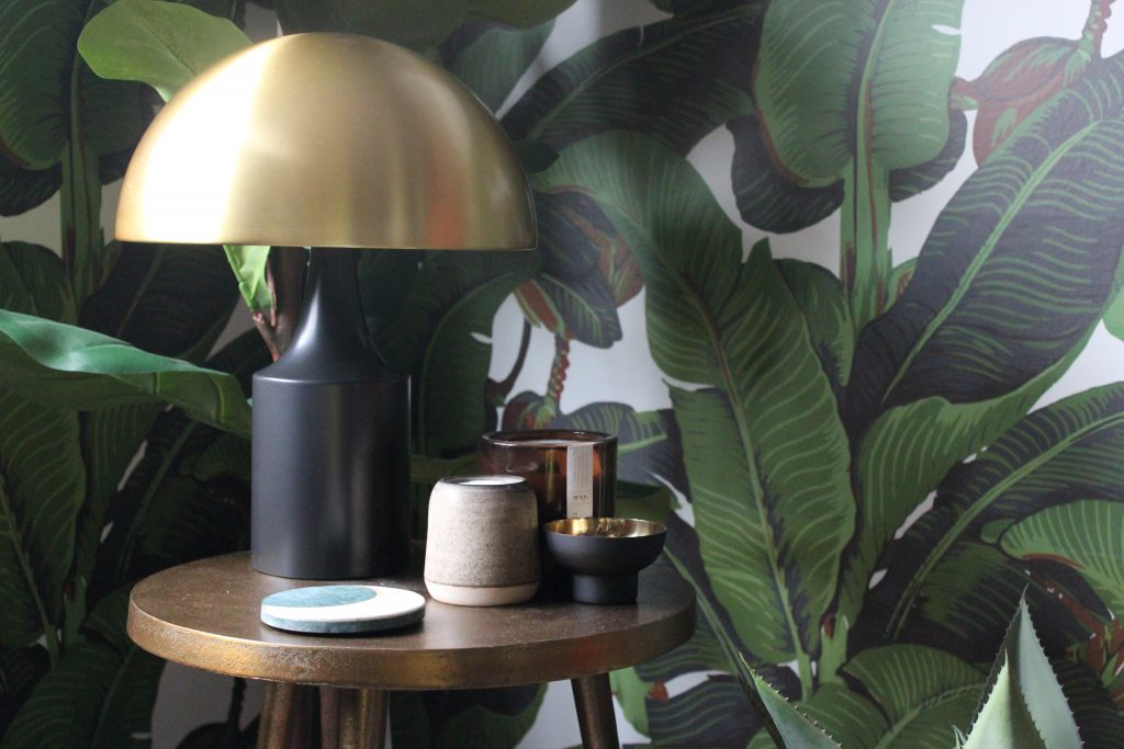a brass lamp and coasters and candles on a bronze table against botanical wallpaper