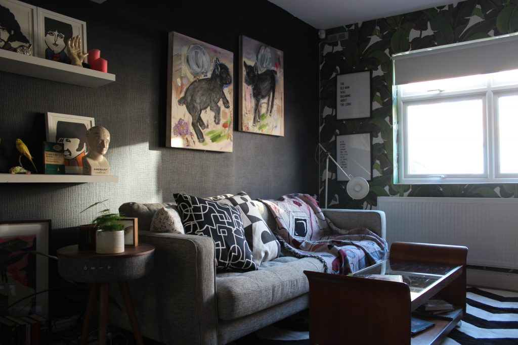 black wall, grey sofa, art of goats, monochrome cushions, zig zag rug and coffee table