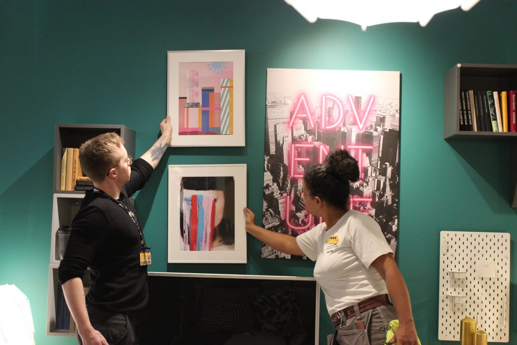 people hold up pink art prints on a  green wall,