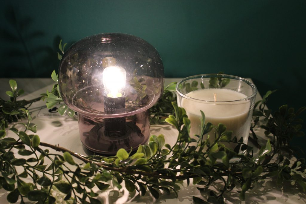 pink lamp and candle with festive foliage around it