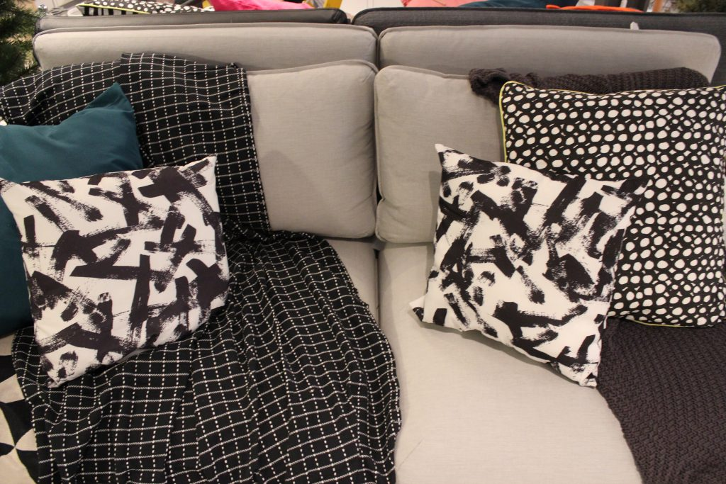 black and white dot and paint splash and green cushions on a grey sofa